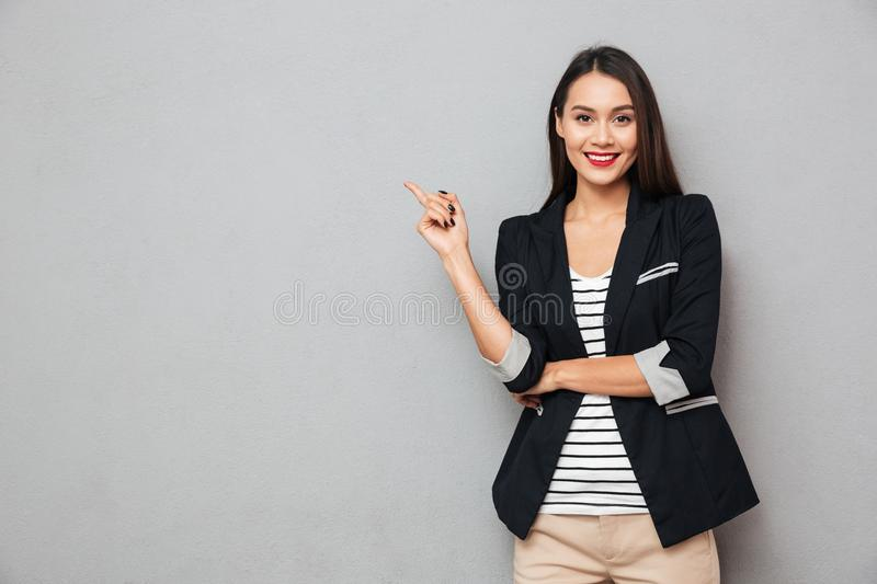 Smiling asian business woman pointing up and looking at camera. Smiling asian business woman pointing up and looking at the camera over gray background
