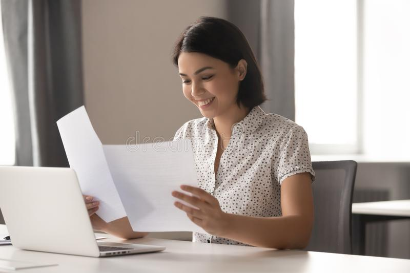 Smiling asian business woman satisfied with new project first results. royalty free stock image