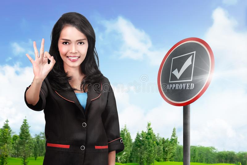 Smiling asian business woman showing OK sign with her hands stock photo