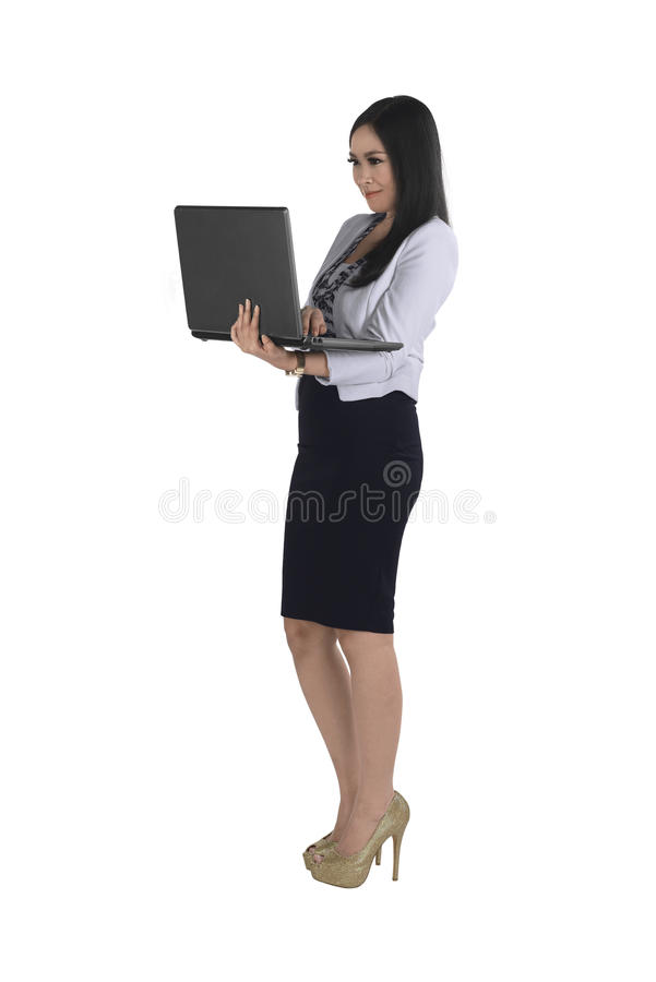 Smiling asian business woman typing while holding laptop. In the street stock image