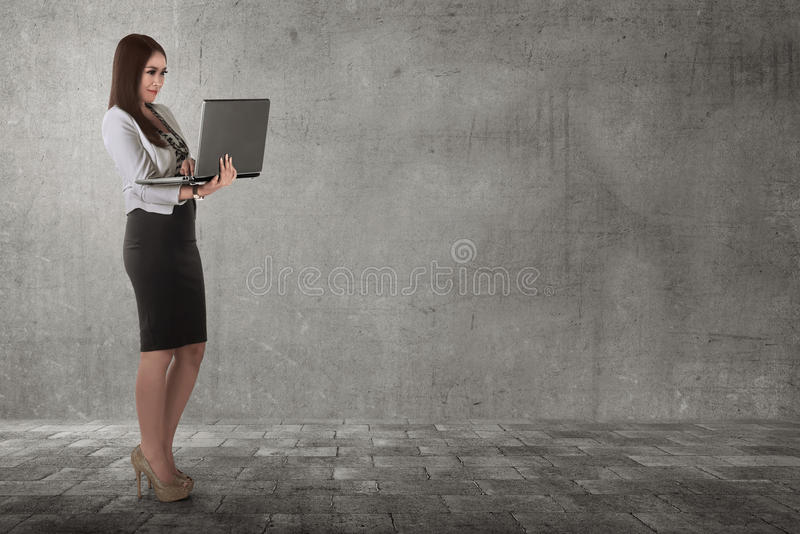 Smiling asian business woman typing while holding laptop. In the street stock photography
