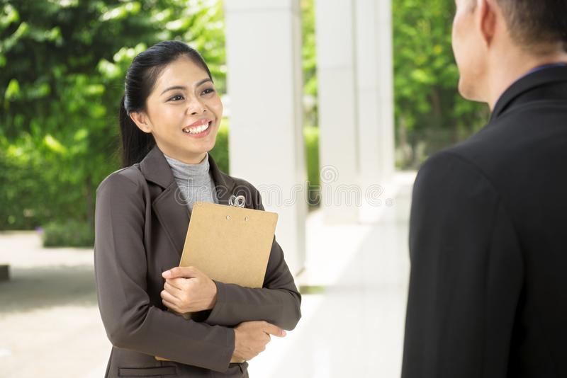 Smiling asian business woman while talking to her business partn royalty free stock photography