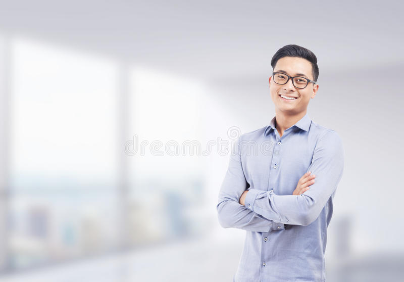 Smiling Asian businessman in blurred office. Smiling Asian businessman in glasses standing with arms folded against blurred office background. Concept of stock photos