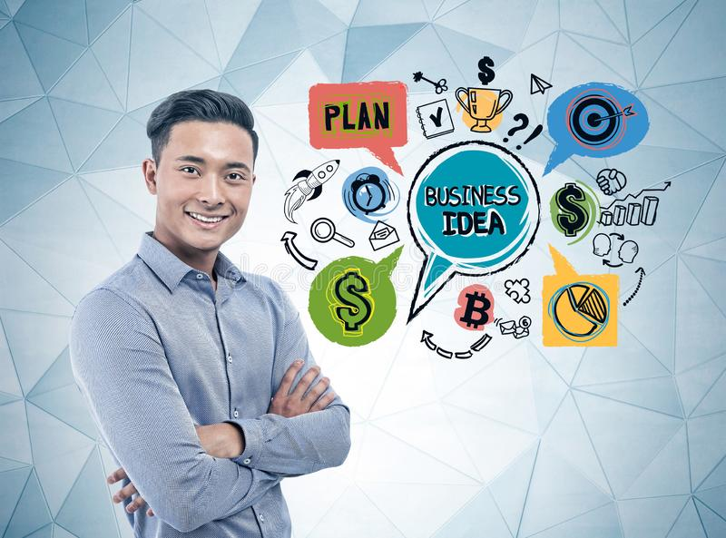 Smiling Asian businessman, business idea. Cheerful young Asian businessman standing with crossed arms near geometric pattern wall with colorful business idea stock images