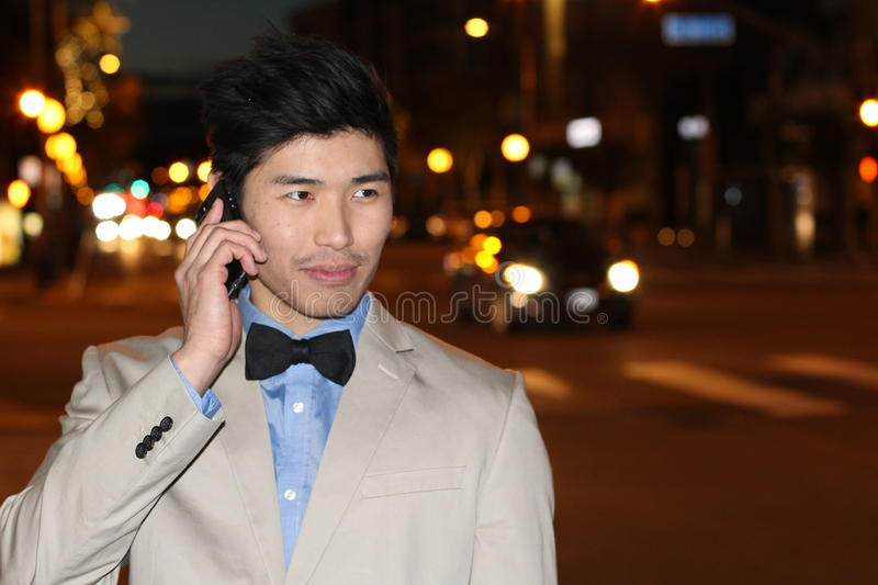 Smiling Asian businessman calling by phone on the street at night - Stock image stock photo