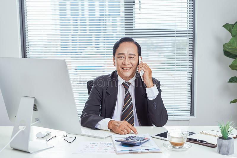 Smiling asian businessman calling someone in office stock photo