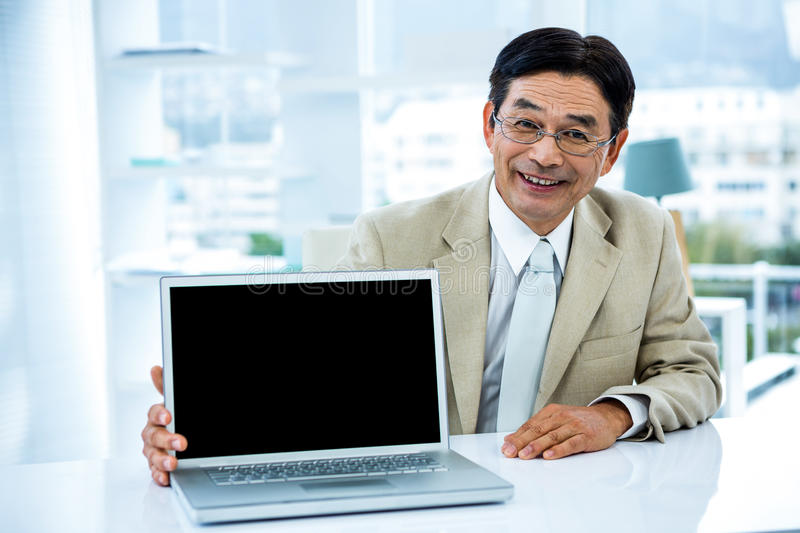 Smiling asian businessman showing his laptop stock photography