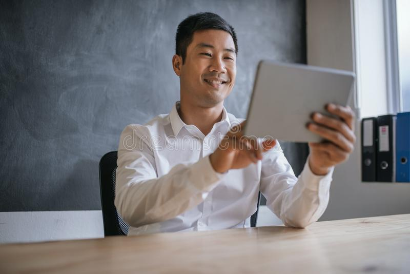 Smiling Asian businessman using a tablet at his office desk stock photo