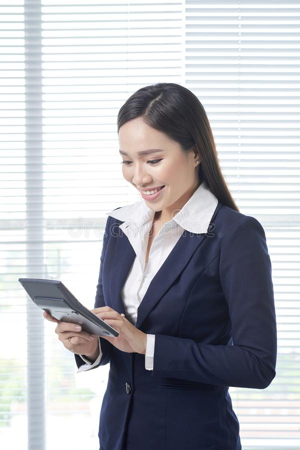 Smiling asian businesswoman in bright office using calculator royalty free stock photo