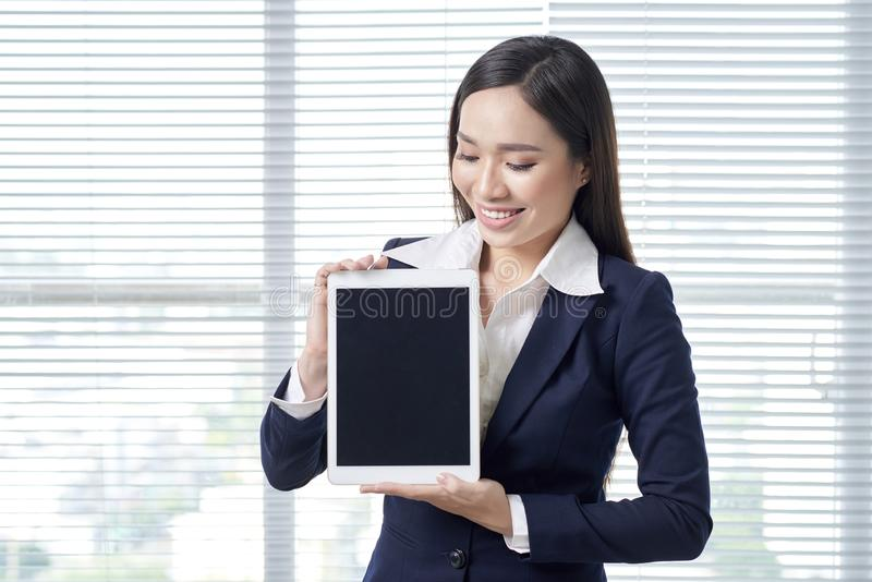 Smiling asian businesswoman in bright office using digital table royalty free stock photos