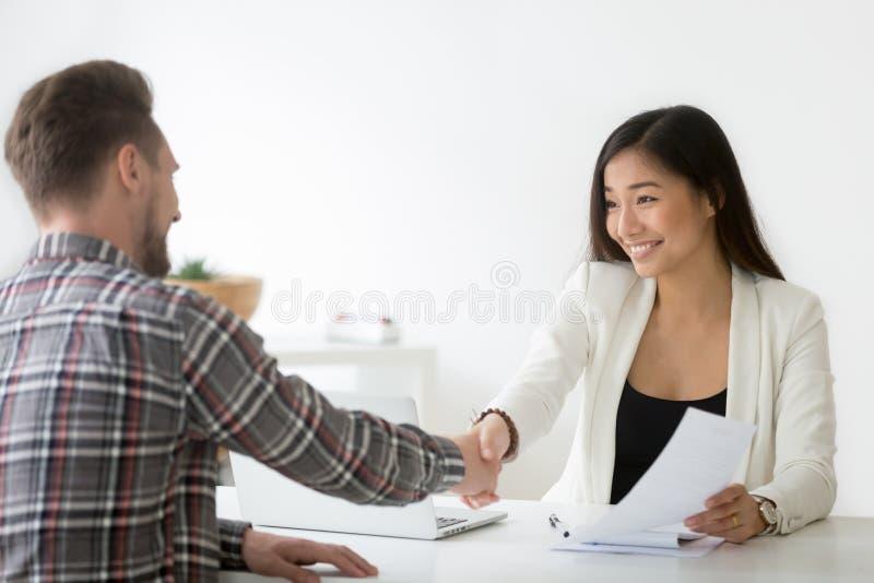 Smiling asian businesswoman handshaking businessman hiring or si. Smiling asian businesswoman handshaking businessman hiring candidate at job interview or stock photo