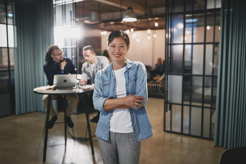 Smiling Asian businesswoman in an office with colleagues behind stock photos