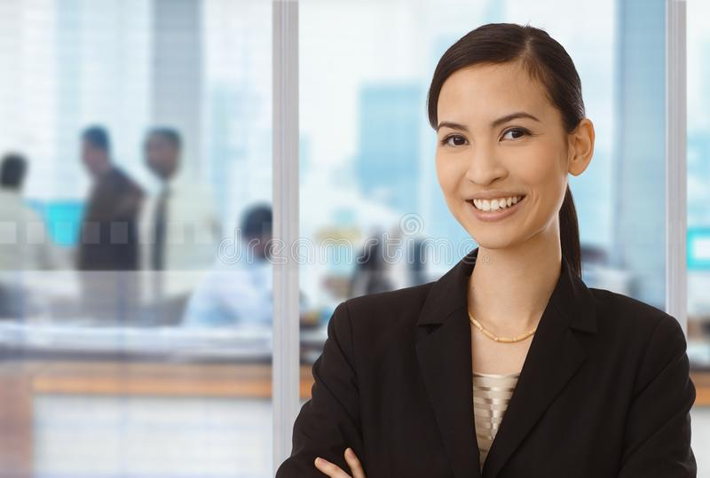Smiling asian businesswoman in office. Portrait of smiling asian businesswoman in office royalty free stock photos