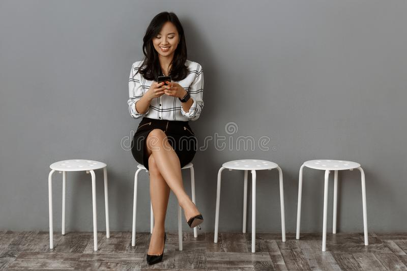smiling asian businesswoman with smartphone waiting stock photography