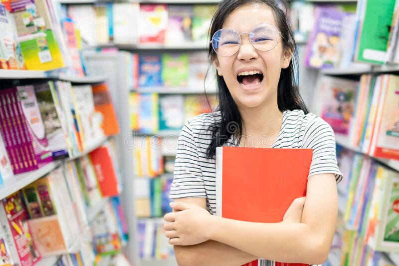 Smiling asian child girl wearing glasses holding a book on her arms,female student standing feel enjoy in book store,happy woman. Is laughing, relax by reading stock photos