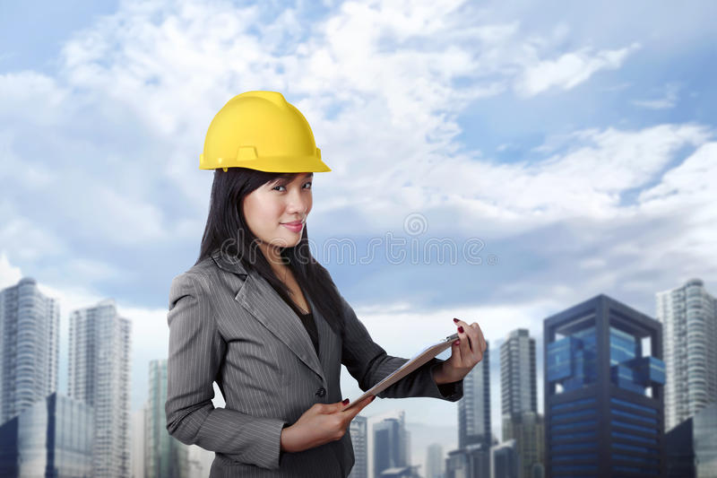 Smiling asian contractor woman with yellow helmet holding clipboard stock photo