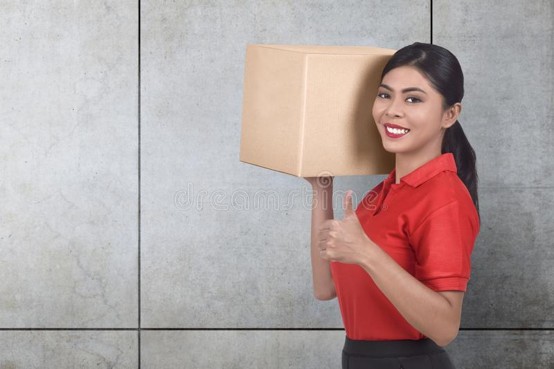 Smiling asian courier woman bring the parcel royalty free stock photos