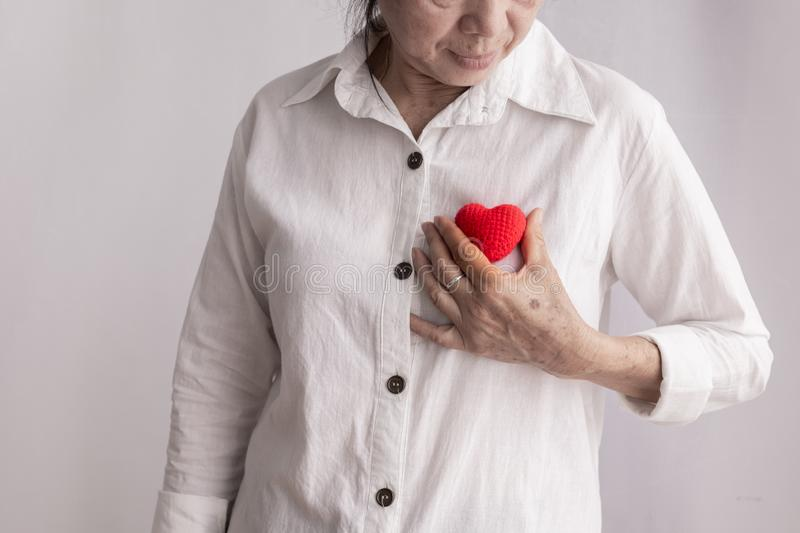 Smiling asian elderly woman holding red heart shape, concept of prevention heart disease stock image