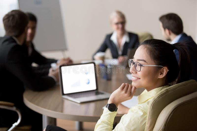 Smiling Asian employee distracted from meeting dreaming of somet royalty free stock photos