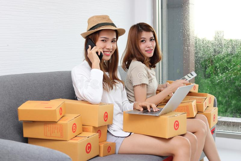 Smiling Asian entrepreneur owner women with cardboard box sitting on modern sofa at home. Online start up business stock images