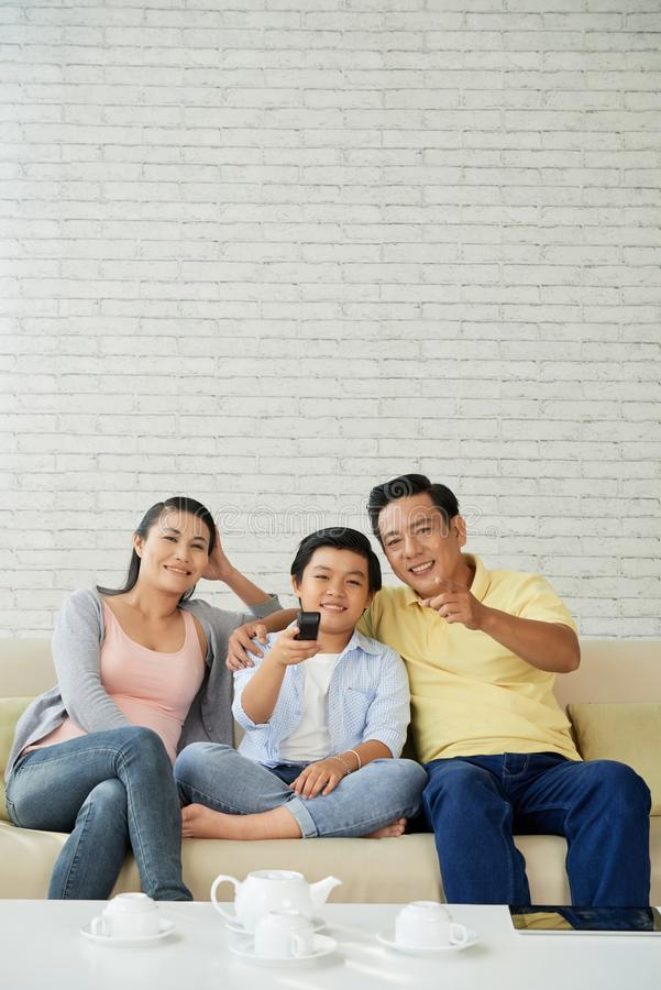 Family watching good movie. Smiling Asian family of three sitting on sofa and enjoying good movie on tv royalty free stock photography