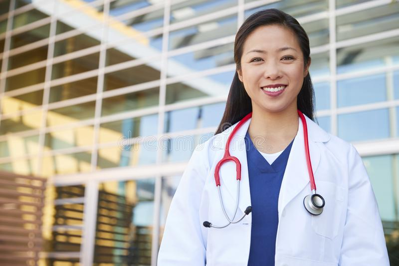 Smiling Asian female healthcare worker outdoors in lab coat royalty free stock photos
