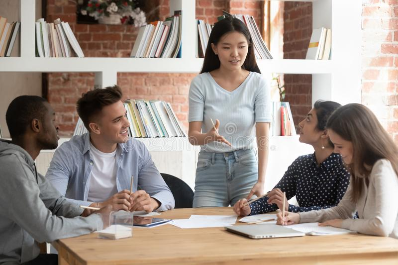 Smiling asian female team leader holding meeting with diverse groupmates. royalty free stock image