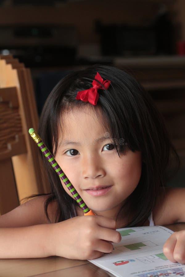 smiling asian girl doing homework stock images