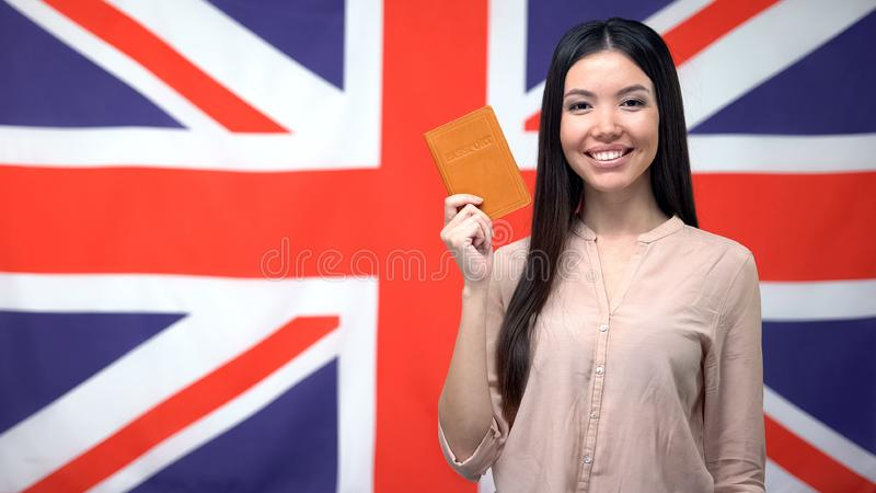 Smiling Asian girl holding passport against British flag background, citizenship royalty free stock photo