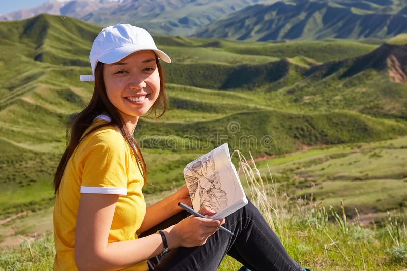 Smiling Asian girl painting the landscape. Painting outdoors. Kazakhstan. Mountain landscape royalty free stock images