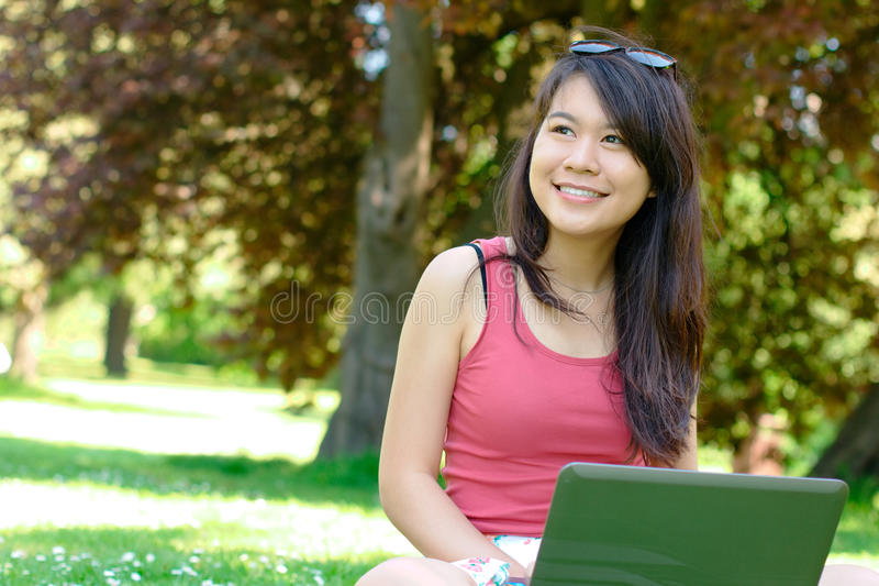 Smiling asian girl at the park royalty free stock photos