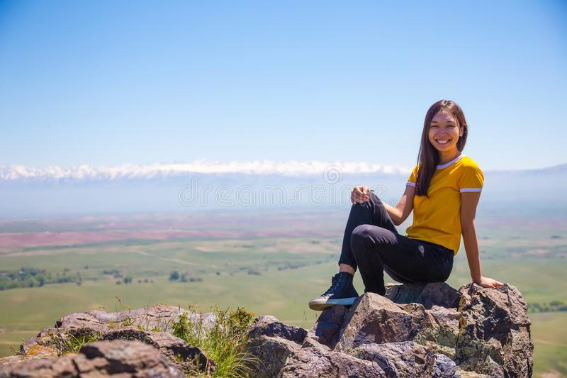A smiling Asian girl sits on a rock against a background of a mountain landscape. Almaty. Kazakhstan royalty free stock images