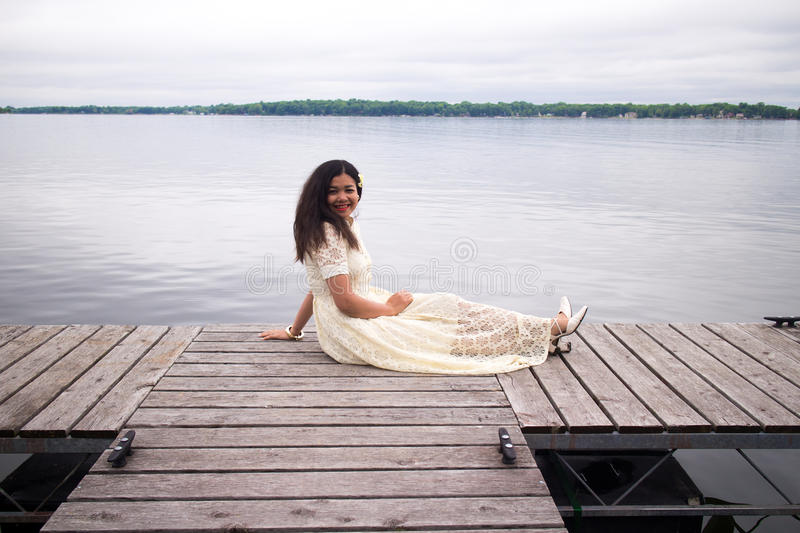Smiling Asian Girl in a White Dress Sitting on a Dock stock image