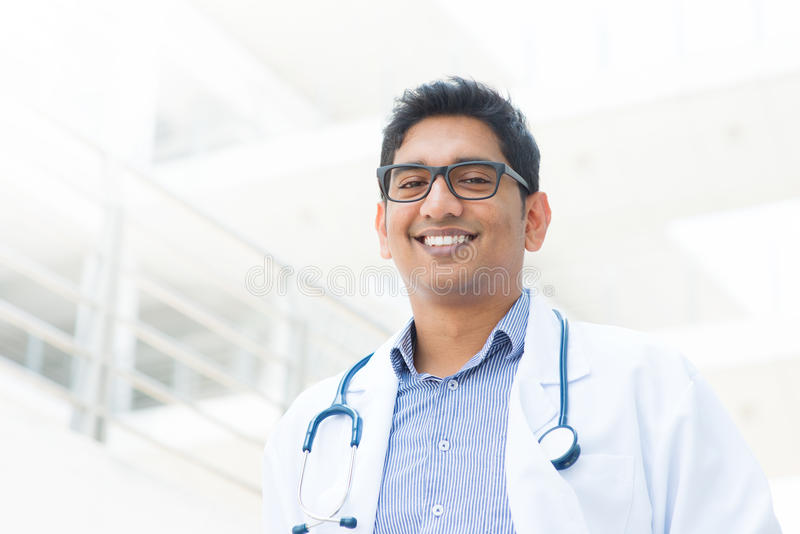 Smiling Asian Indian male medical doctor. Portrait of a smiling Asian Indian male medical doctor in uniform, hospital building at background stock images