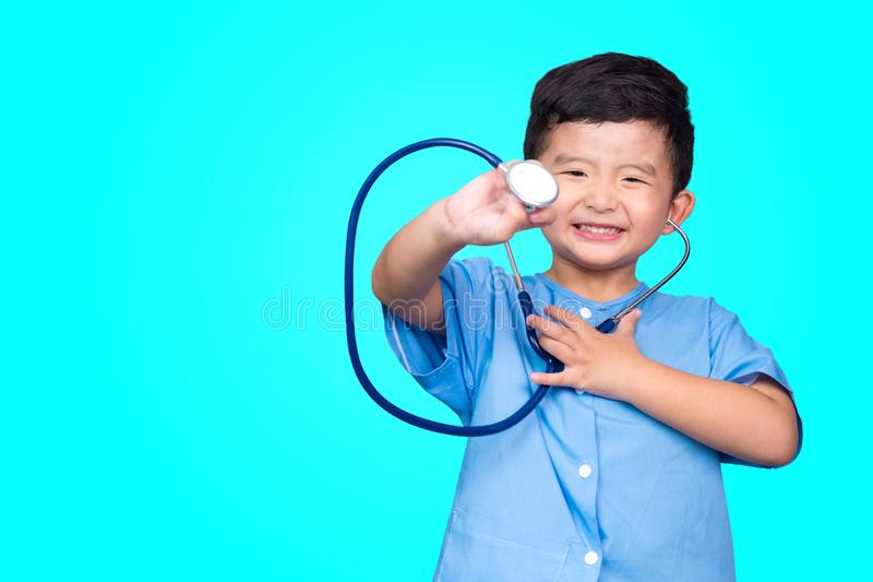 Smiling Asian kid in blue medical uniform holding stethoscope looking at camera on blue green background with copy space, healthy royalty free stock photography