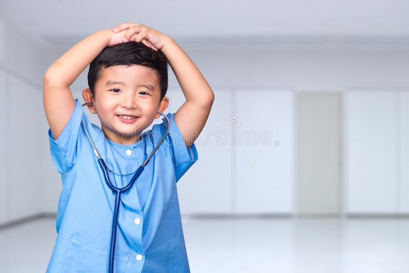 Smiling Asian kid in blue medical uniform holding stethoscope looking at camera, healthy concept stock photography