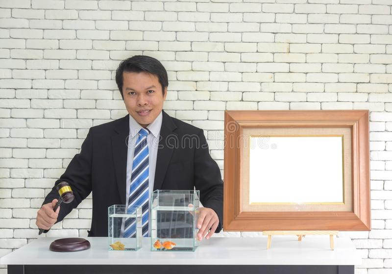 Smiling asian man in black suit with wooden gavel in hand and blank picture frame wait people bidding auction concept.  stock photo