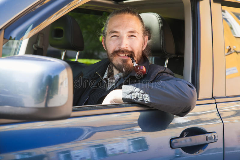 Smiling Asian man smoking pipe. Driver. Of modern Japanese crossover suv car, portrait in open car window royalty free stock photo