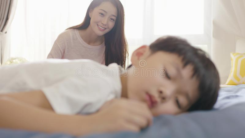 Smiling Asian mother looking at his son in sleep in the morning stock images