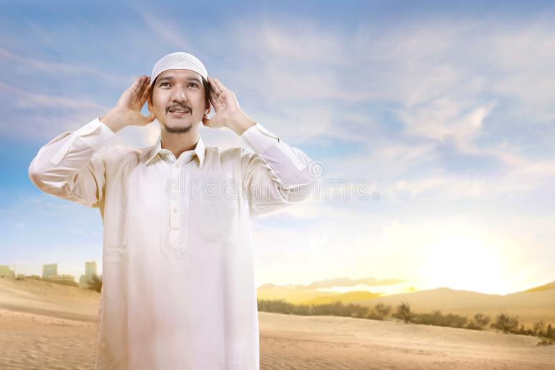 Smiling asian muslim man with cap standing and praying on the sand. With blue sky background royalty free stock photo