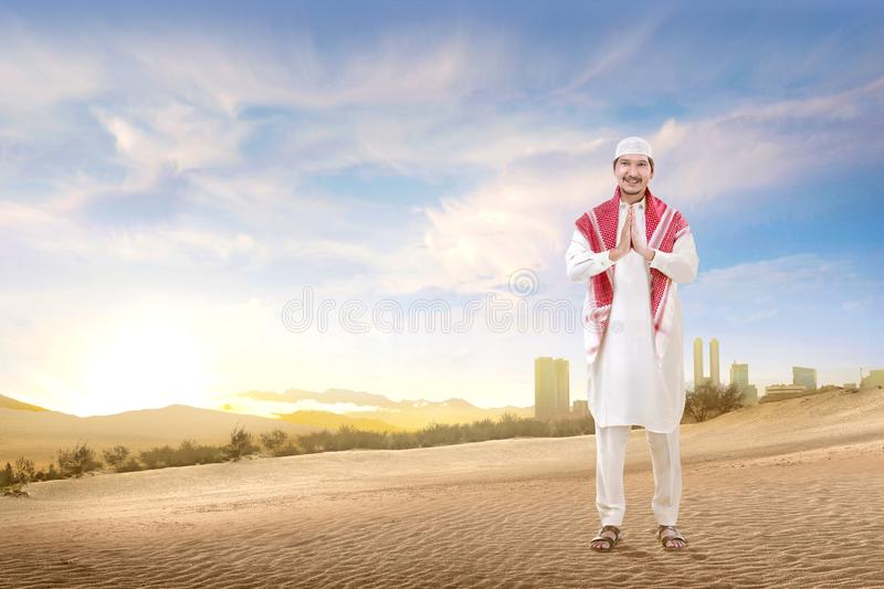 Smiling asian muslim man with cap and turban standing and praying on the sand. With blue sky background stock image