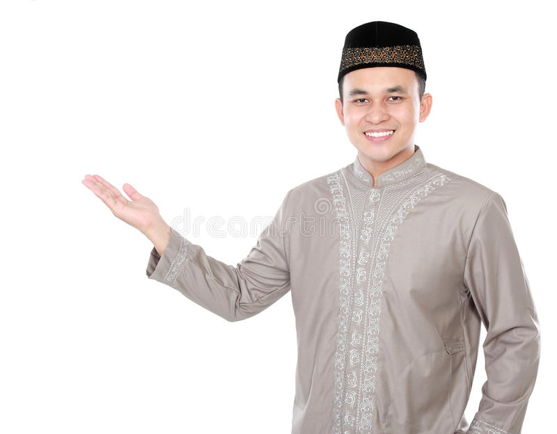 Smiling asian muslim man presenting copy space stock image