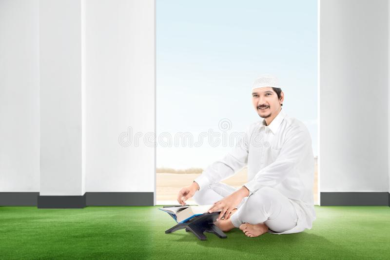 Smiling asian muslim man sitting on the carpet with koran inside the room. With open door and blue sky background stock image