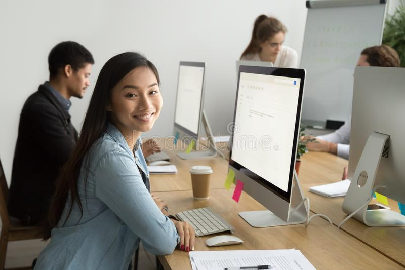 Smiling asian office employee looking at camera working with col stock photo