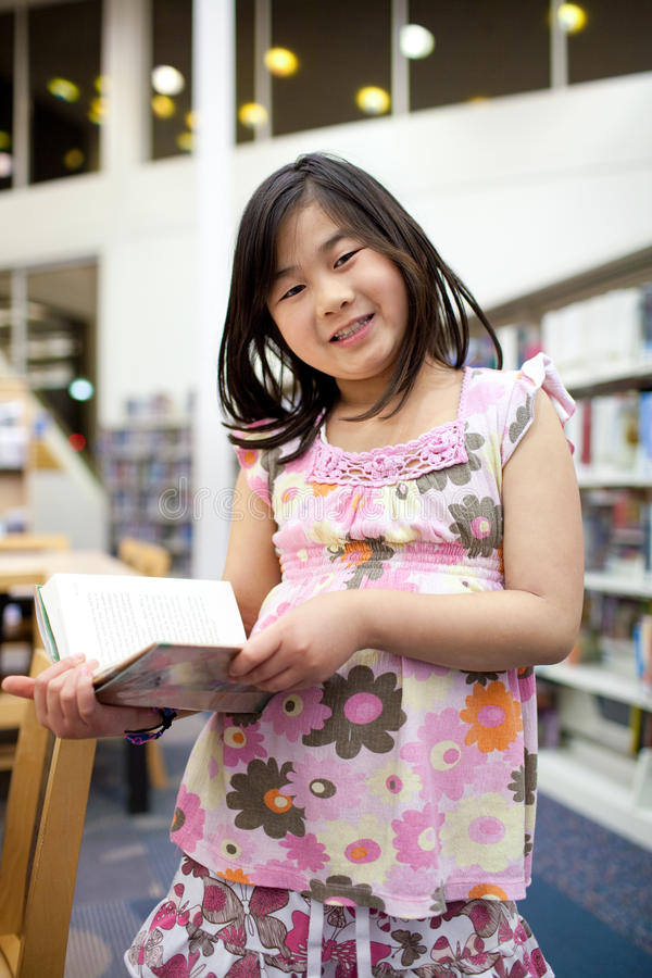 Smiling Asian School Girl Reading Book at Library