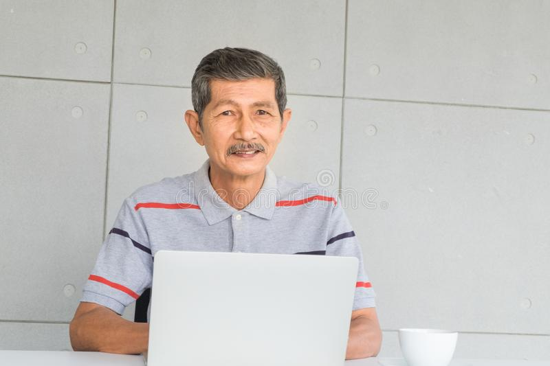 Smiling, Asian senior man. Dress with casual clothes sitting and working on the table with  laptop computer and white coffee mug, royalty free stock images