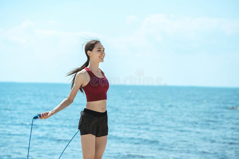 smiling asian sportswoman doing exercise with jump rope in front of royalty free stock image