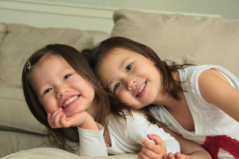 Smiling asian toddler sisters laying on stomach on couch. Biracial Asian toddler sisters laying on stomach on a couch with their heads together. Sisters a stock images