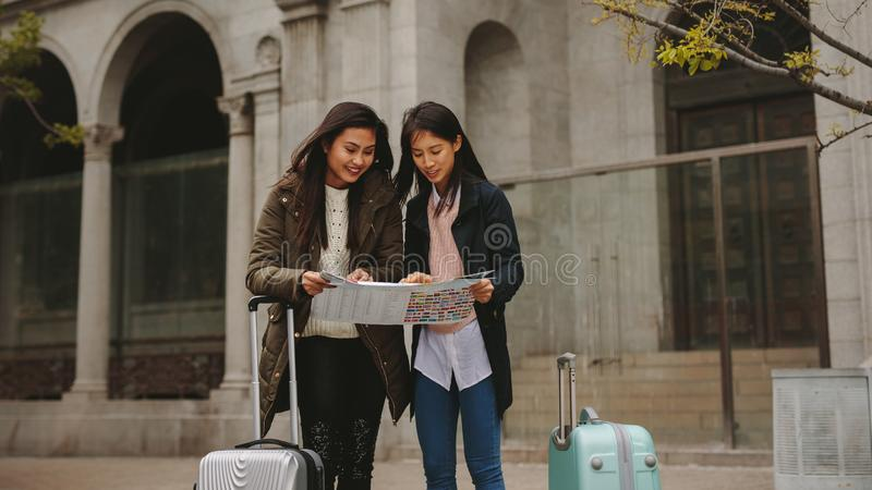 Smiling asian tourists looking at a city map royalty free stock images