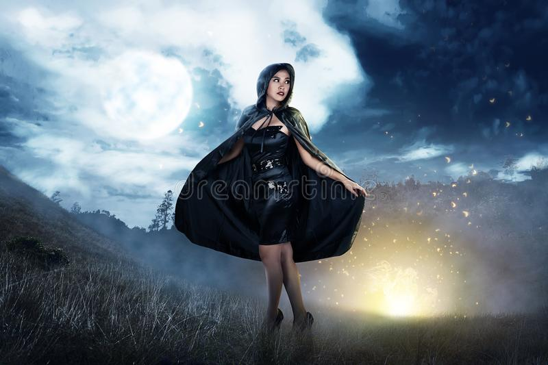 Smiling asian witch woman with black hooded cloak standing. At night royalty free stock photography